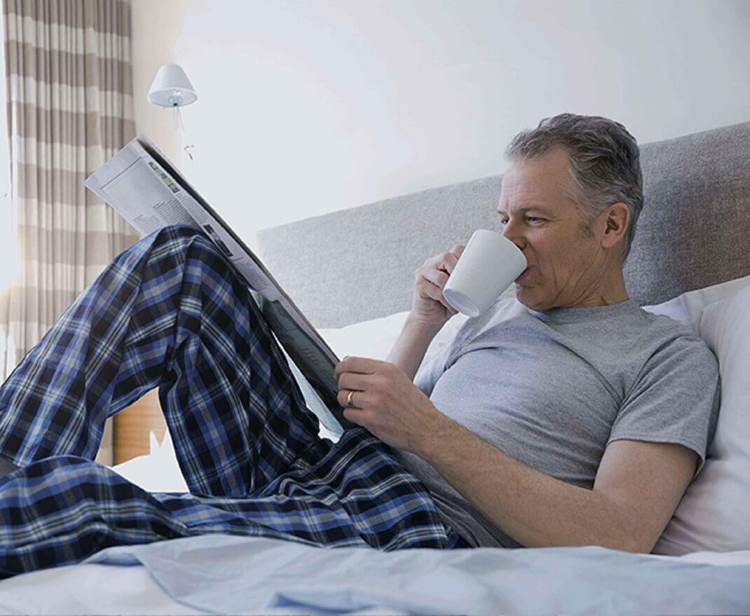 An older man in his pajamas in bed, drinking coffee and reading the newspaper