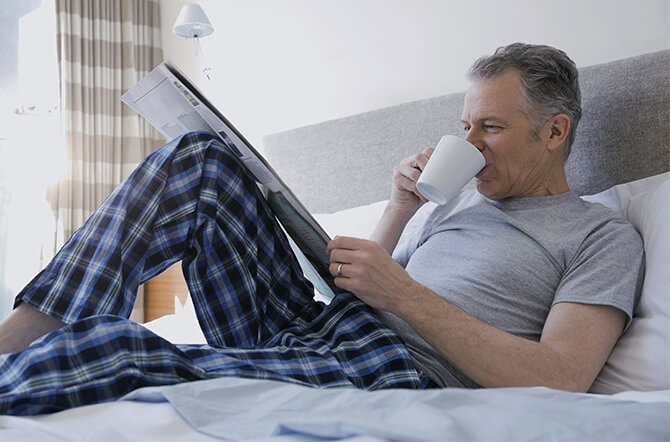 An older man in his pajamas in bed, drinking coffee and reading the newspaper Mobile