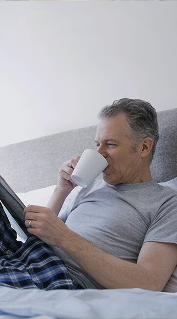 An older man in his pajamas in bed, drinking coffee and reading the newspaper Tablet Portrait