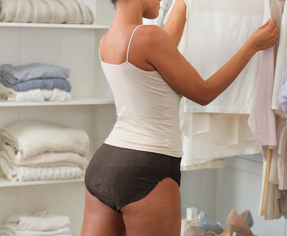 Female standing wearing Depend Silhouette Briefs and tank top holding a blouse.